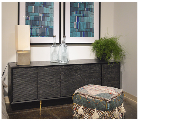 Black wash wood sideboard in room setting with pouf in front and blue wall art