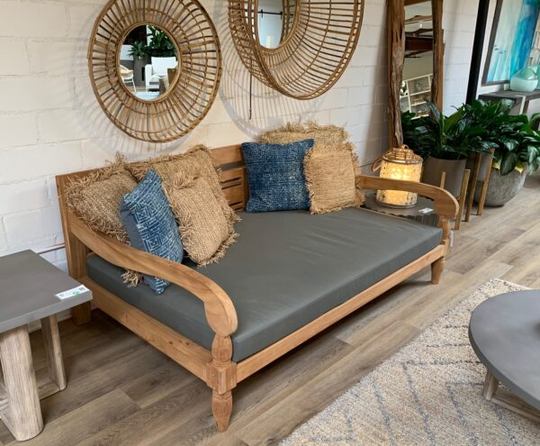 Outdoor teak daybed with cushion in patio setting