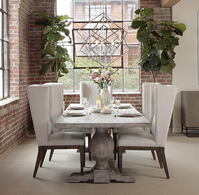 Grey wash trestle dining table with white wing chairs in room with brick wall