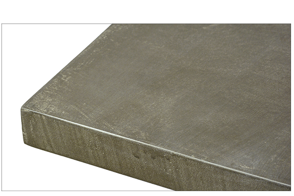 Dining table with concrete laminate top and wood base close up