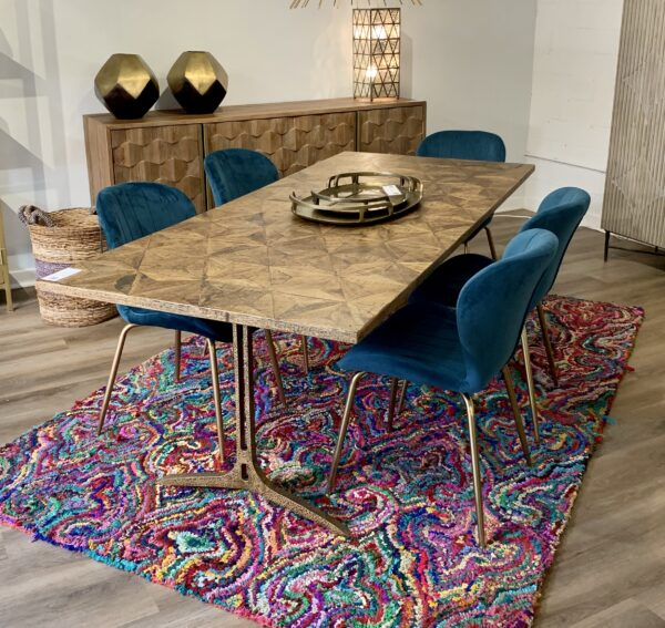 Dining table with iron base in brass finish and blue dining chairs