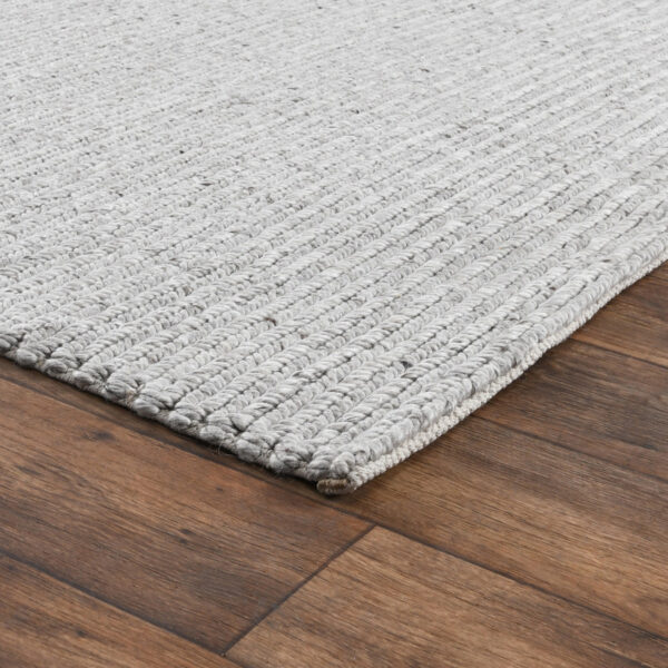 light grey woven rug on wood floor