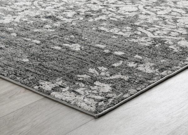 black and grey patterned rug on wood floor