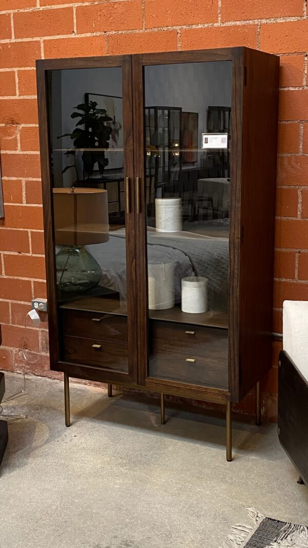 Dark wood tall cabinet with glass doors and brass color iron legs