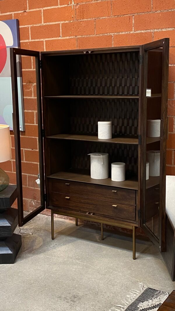 Dark wood tall cabinet with glass doors and brass color iron legs shown with open doors