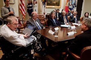 Man with assistive technology device at table with President Obama
