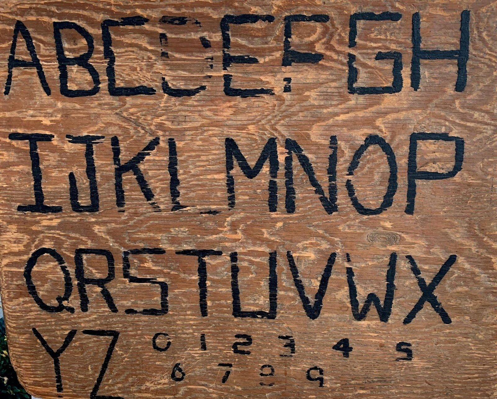 wood plank hand-carved with capital letters A-Z and numbers