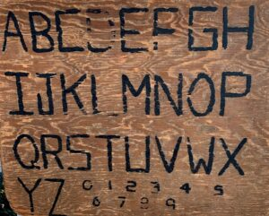 wood plank arved with capital letters A-Z and numbers 0-9