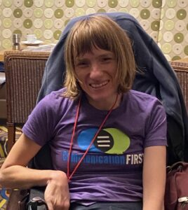 Melissa Crisp-Cooper smiling, sitting in a wheelchair, wearing a purple t-shirt with the CommunicationFIRST logo.