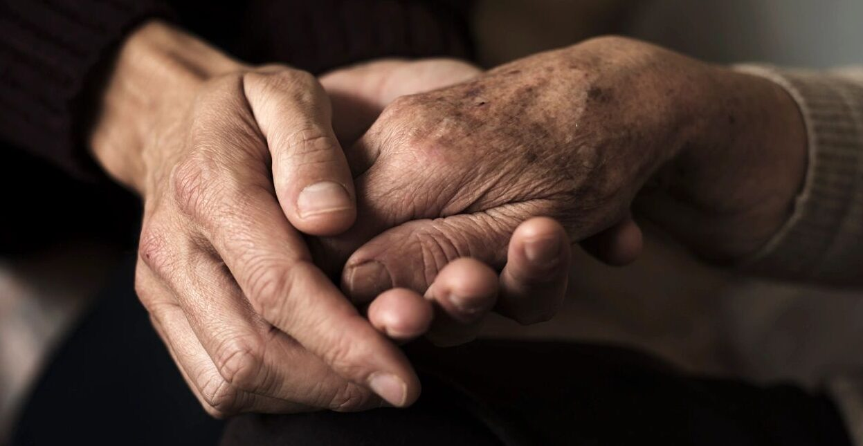 sepia-colored image of two hands holding another