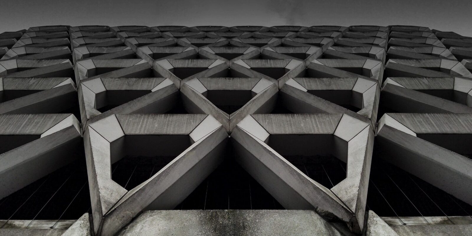 artsy black and white stock photo looking upward at modernist concrete scaffolding on the outside of a building