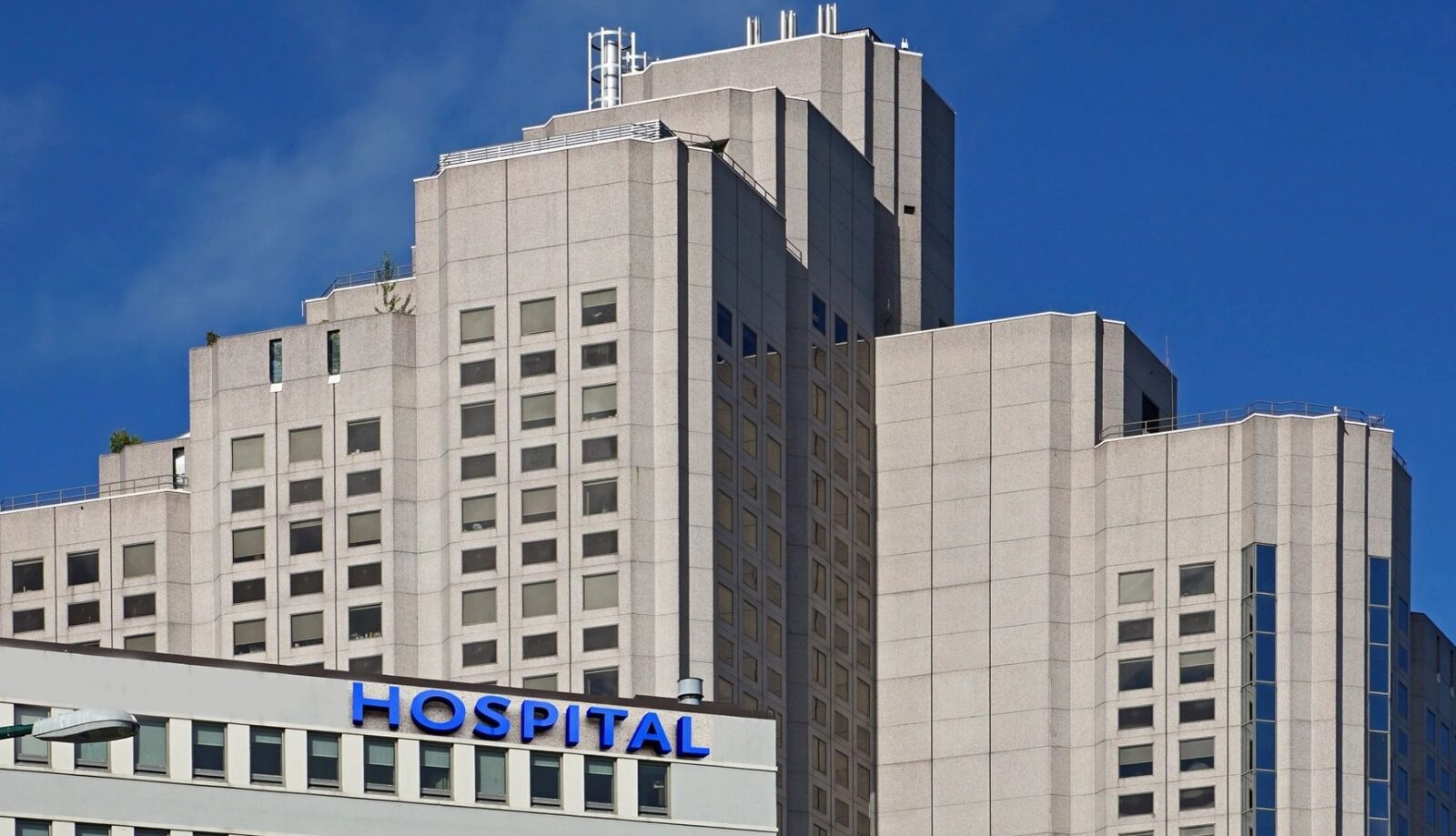 tall white facade buildings against a blue sky; one building has the word hospital in blue letters