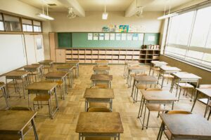 empty old style classroom with wooden desks, wood floor, and green blackboard