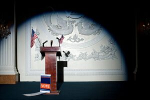 "image of empty lectern with American flags and a ""Vote"" placard"