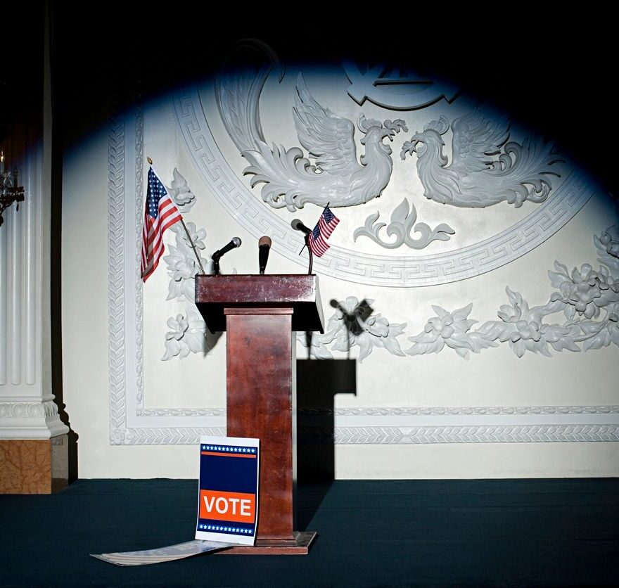 """image of empty lectern with American flags and a """"Vote"""" placard"""