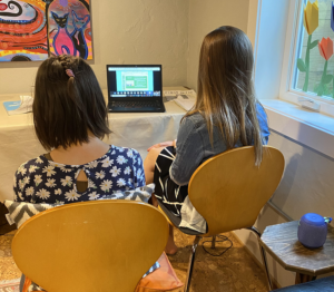 a middle-school-aged girl with shoulder-length brown hair wearing a flowery top sits facing a laptop screen. To her right is an adult aide with long straight light brown hair wearing a jean jacket. Their backs are to the camera.