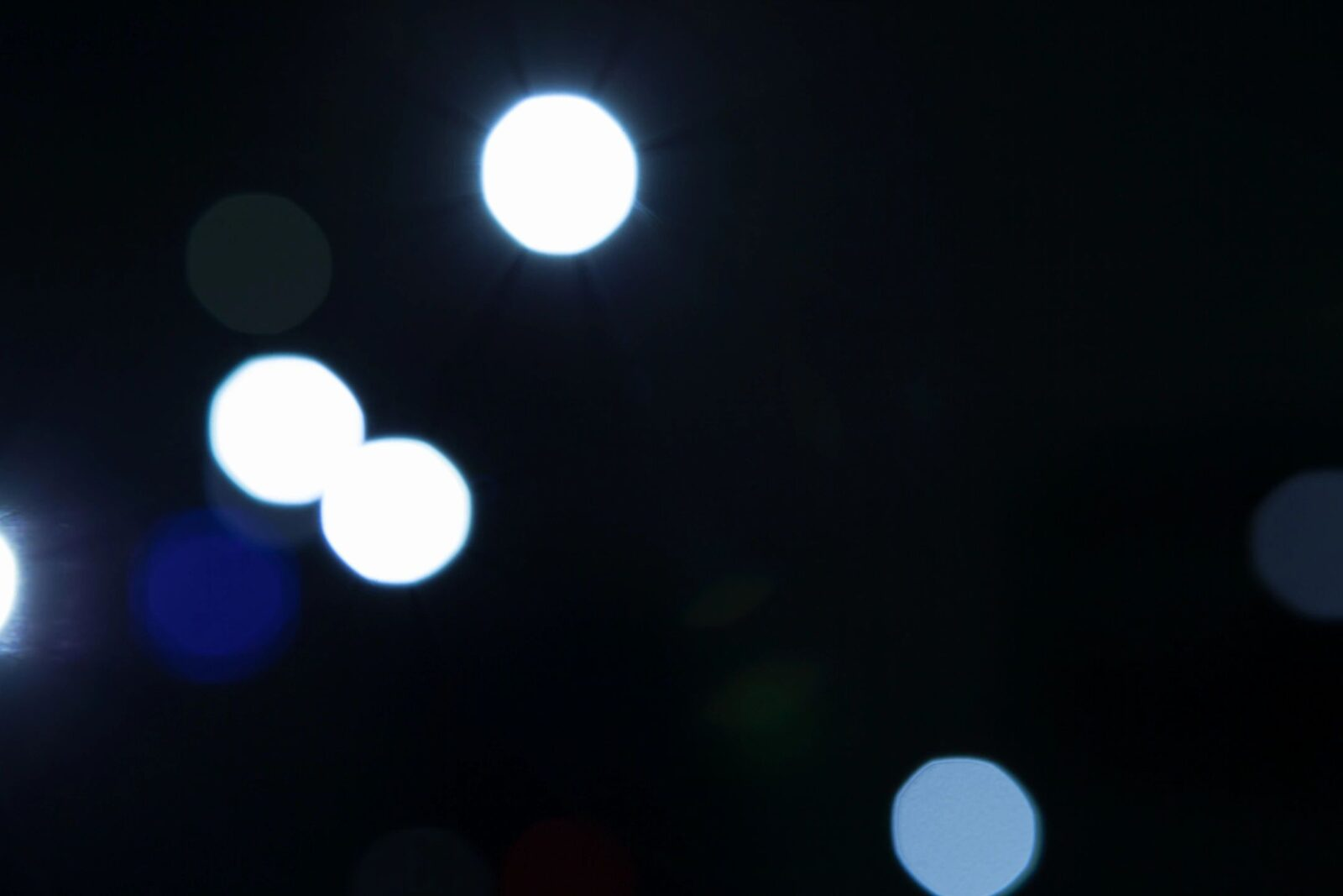 blurry white and blue lights on a black background