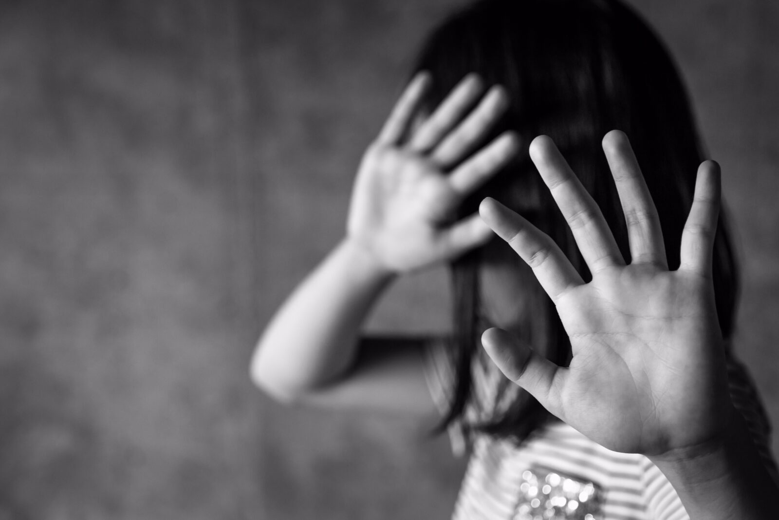 black and white image of a child with straight, black, shoulder-length hair whose face is not visible behind their outstretched palms as if they are saying no with their hands