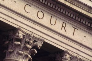 """stock photo image of the top of the outside of a building with the word """"court"""" engraved in the marble"""
