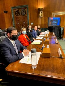 A photo of five witnesses wearing suits seated before a long wooden table with papers in front of them in a US Senate Judiciary Subcommittee hearing room. One of the witnesses is Dr. Clarissa Kripke, wearing a red jacket. Four of the five witnesses are wearing masks. Four of the five witnesses are looking at the camera and appear to be smiling underneath their masks.