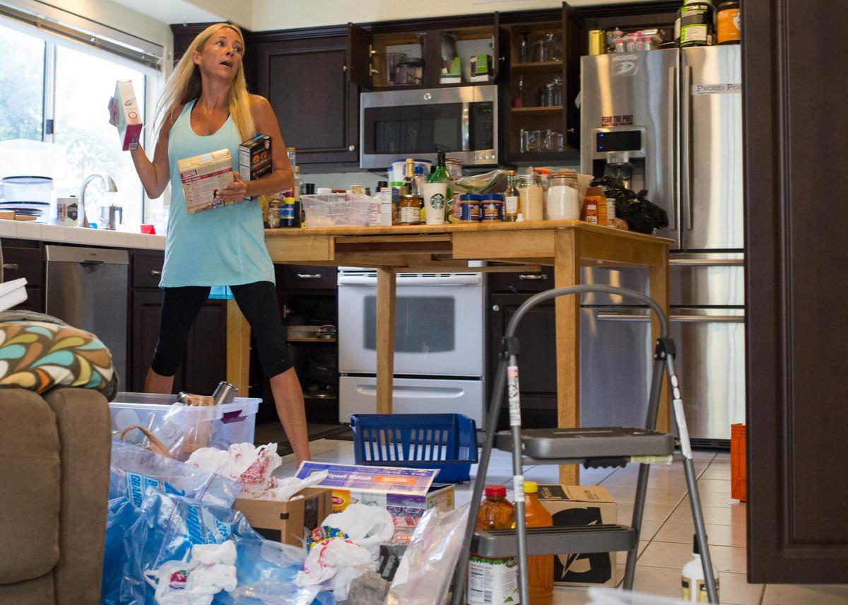 """Professional organizer Kirsten Ranger of Organized & Orderly navigates around the contents of a kitchen pantry while decluttering at a private residence in Trabuco Canyon on Tuesday. ////ADDITIONAL INFORMATION: lansner.declutter - 7/7/15 - JOSH BARBER, - ORANGE COUNTY REGISTER - at on Tuesday, July 7, 2015 in Trabuco Canyon, Calif. Columnist Jon Lansner will have a room in his home """"decluttered"""" by decluttering expert Kirsten Ranger of Organized & Orderly of Organized & Orderly"""