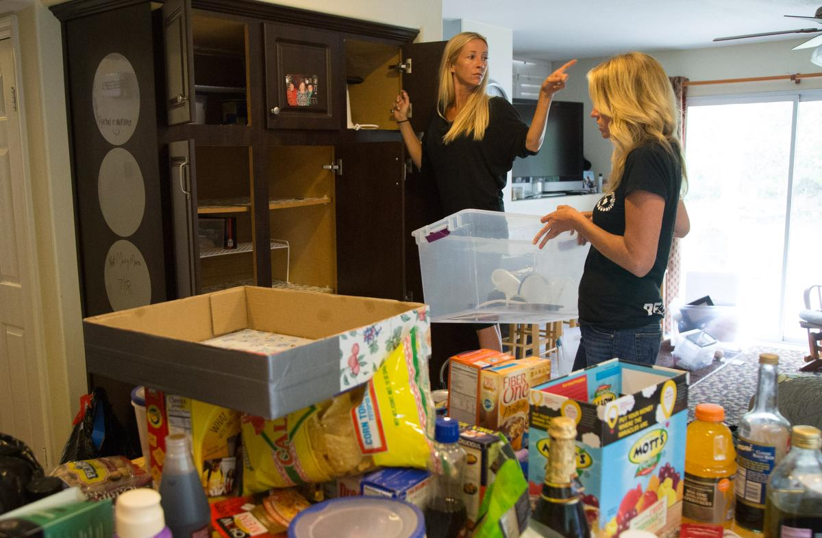 """Professional organizer Kirsten Ranger of Organized & Orderly and her assistant Allison Richards begin to work on a pantry while decluttering a kitchen at a private residence in Trabuco Canyon on Tuesday. ////ADDITIONAL INFORMATION: lansner.declutter - 7/7/15 - JOSH BARBER, - ORANGE COUNTY REGISTER - at on Tuesday, July 7, 2015 in Trabuco Canyon, Calif. Columnist Jon Lansner will have a room in his home """"decluttered"""" by decluttering expert Kirsten Ranger of Organized & Orderly of Organized & Orderly"""