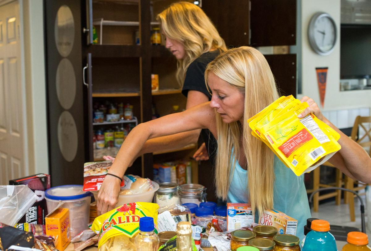 """Professional organizer Kirsten Ranger of Organized & Orderly and her assistant Allison Richards sort through food stored in a pantry while decluttering a kitchen at a private residence in Trabuco Canyon on Tuesday. ////ADDITIONAL INFORMATION: lansner.declutter - 7/7/15 - JOSH BARBER, - ORANGE COUNTY REGISTER - at on Tuesday, July 7, 2015 in Trabuco Canyon, Calif. Columnist Jon Lansner will have a room in his home """"decluttered"""" by decluttering expert Kirsten Ranger of Organized & Orderly of Organized & Orderly"""