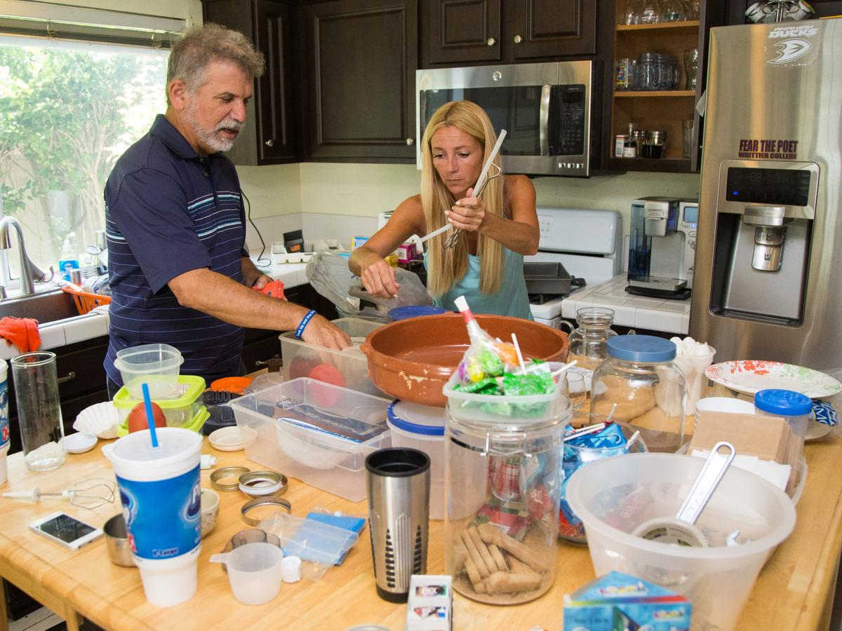 """Orange County Register writer Jonathan Lansner and Professional organizer Kirsten Ranger of Organized & Orderly sort through cooking implements while decluttering a kitchen at a private residence in Trabuco Canyon on Tuesday. ////ADDITIONAL INFORMATION: lansner.declutter - 7/7/15 - JOSH BARBER, - ORANGE COUNTY REGISTER - at on Tuesday, July 7, 2015 in Trabuco Canyon, Calif. Columnist Jon Lansner will have a room in his home """"decluttered"""" by decluttering expert Kirsten Ranger of Organized & Orderly of Organized & Orderly"""