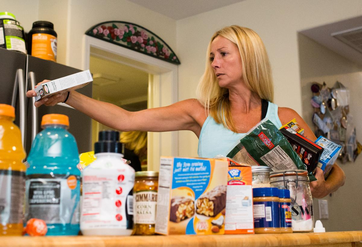 "Professional organizer Kirsten Ranger of Organized & Orderly checks the expiration date on a box of Matzo Ball Soup Mix while decluttering a kitchen pantry at a private residence in Trabuco Canyon on Tuesday. ////ADDITIONAL INFORMATION: lansner.declutter - 7/7/15 - JOSH BARBER, - ORANGE COUNTY REGISTER - at on Tuesday, July 7, 2015 in Trabuco Canyon, Calif. Columnist Jon Lansner will have a room in his home ""decluttered"" by decluttering expert Kirsten Ranger of Organized & Orderly of Organized & Orderly"