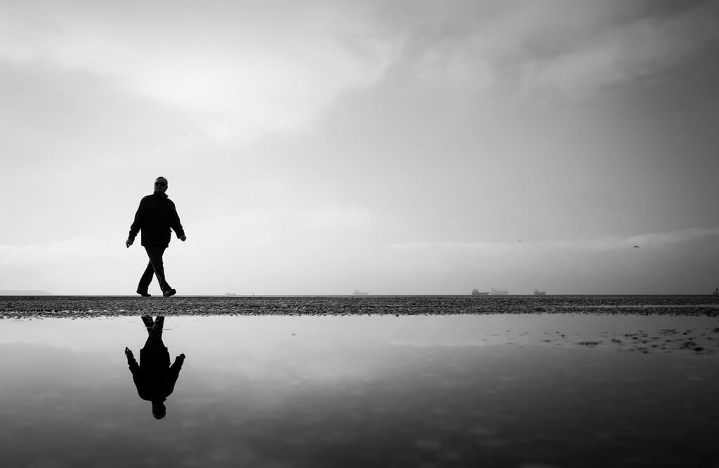 Minimalist walking on the beach black and white