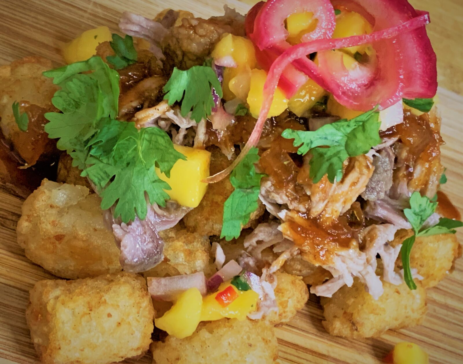 Our fully plated Kalua-Style Pulled Pork Tots with Polynesian BBQ Sauce & Mango Salsa