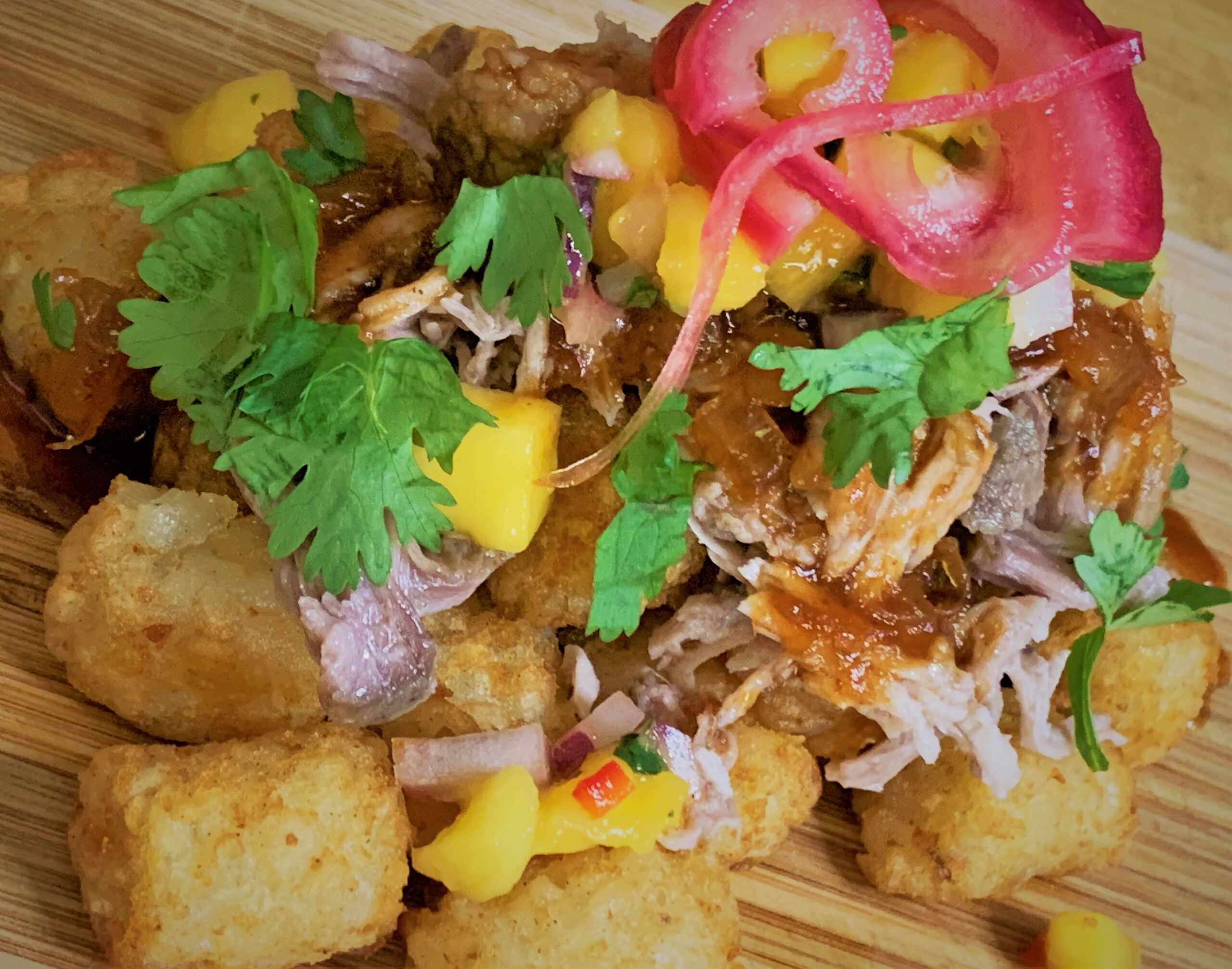 Our fuly plated Kalua-Style Pulled Pork Tots with Polynesian BBQ Sauce & Mango Salsa