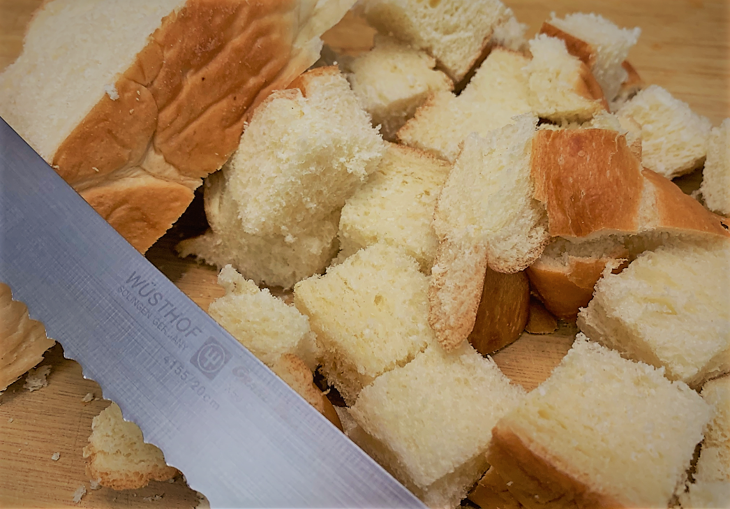 Cubing the Bread for our Boma French Toast Bread Pudding with Pecan Praline Sauce