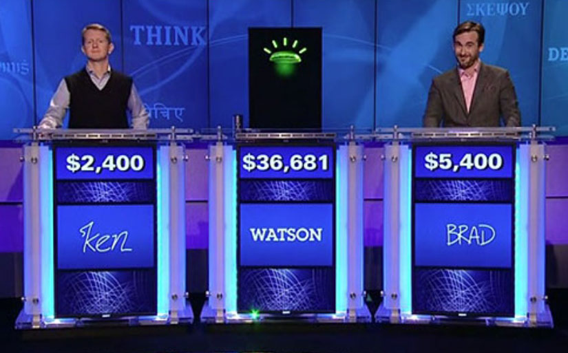 """Image of Jeopardy set with two human contestants flanking """"Watson"""""""