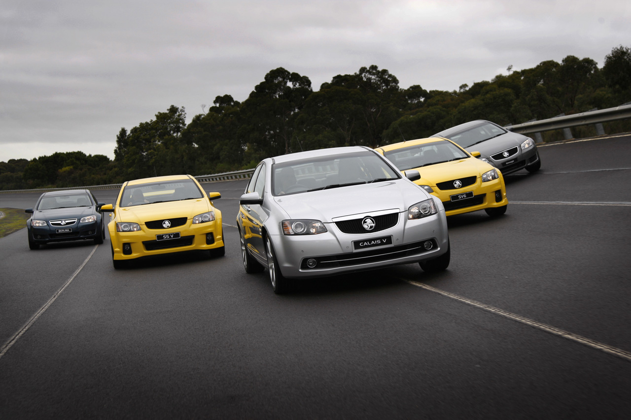 Five new autos on highway in flying V formation