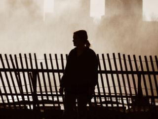 Woman walking along wooden fence
