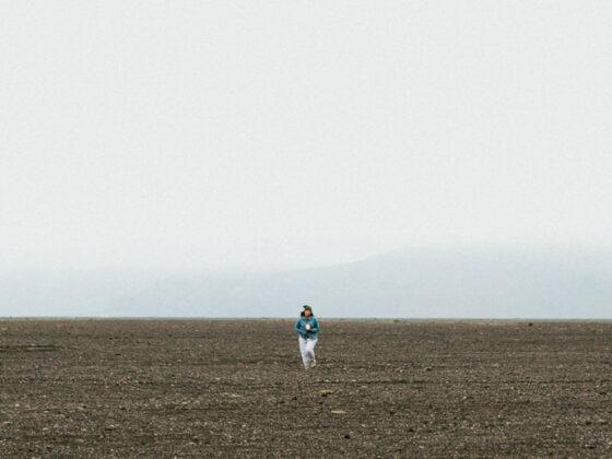Woman walking across barren land