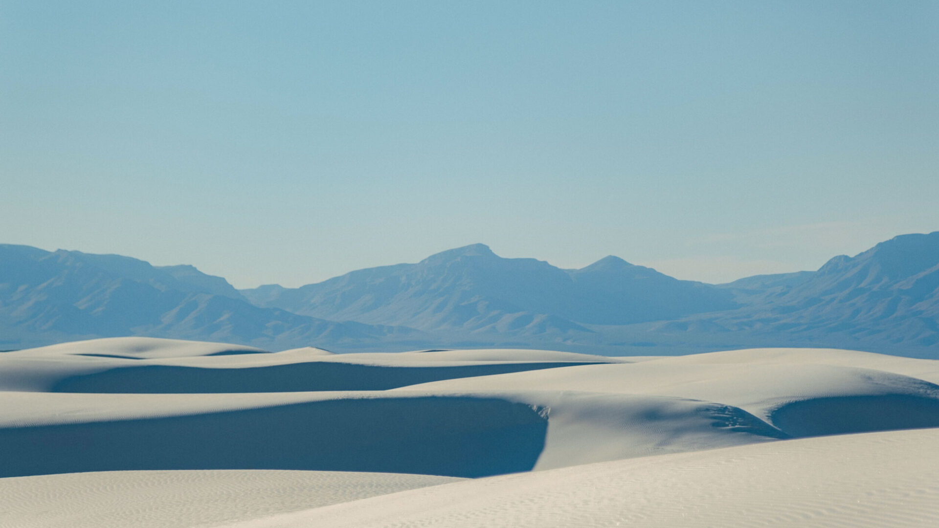 Desert sand with mountains in the background