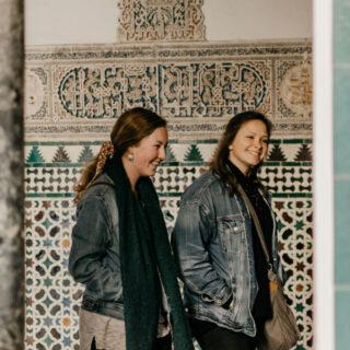 Two girls walking next to Turkish building