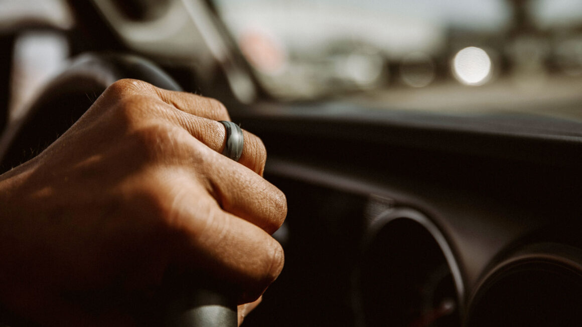 Close-up of hand on steering wheel