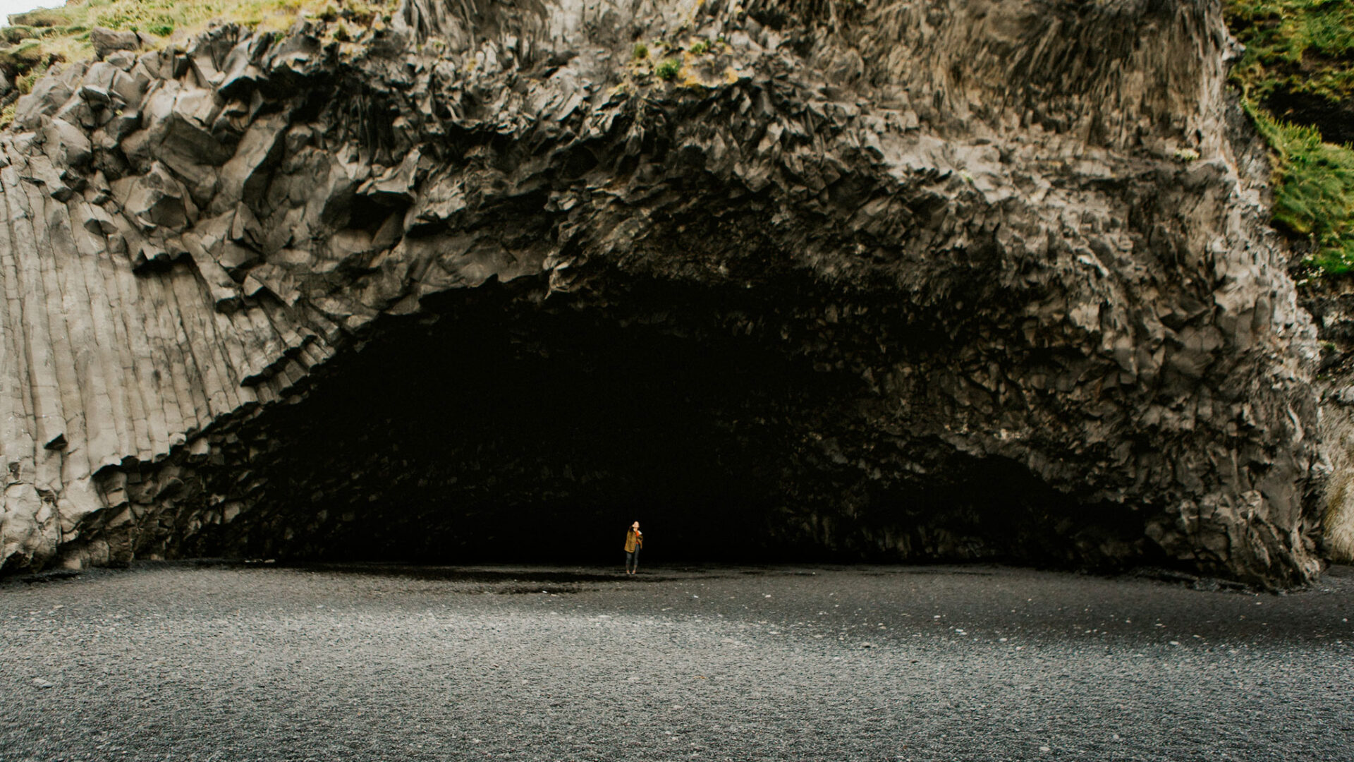 Person standing in large cave entrance