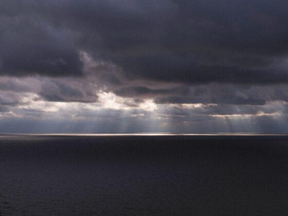 Sun rays shining through dark clouds over water
