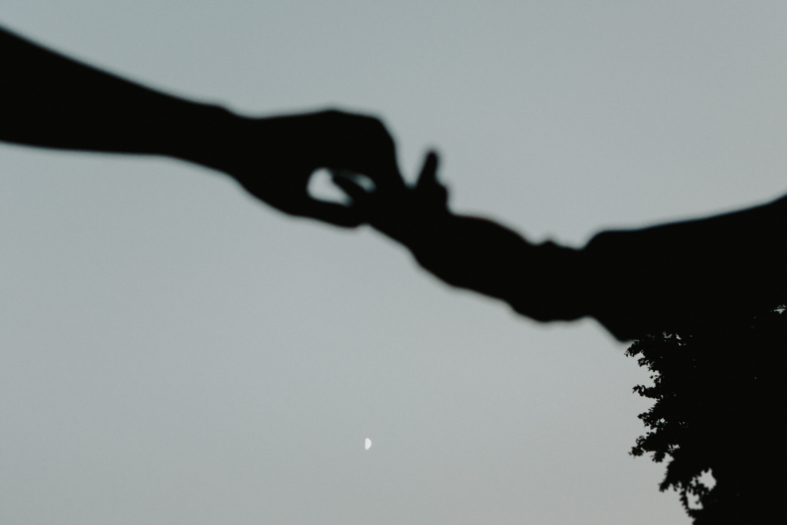 Silhouette of two hands reaching for one another