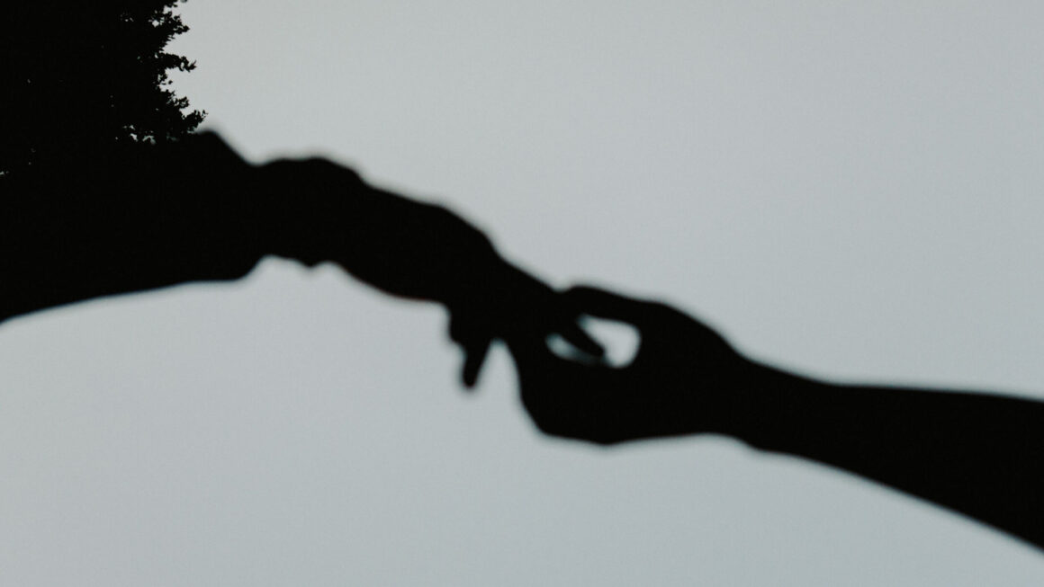 Silhouette of two hands reaching to one another