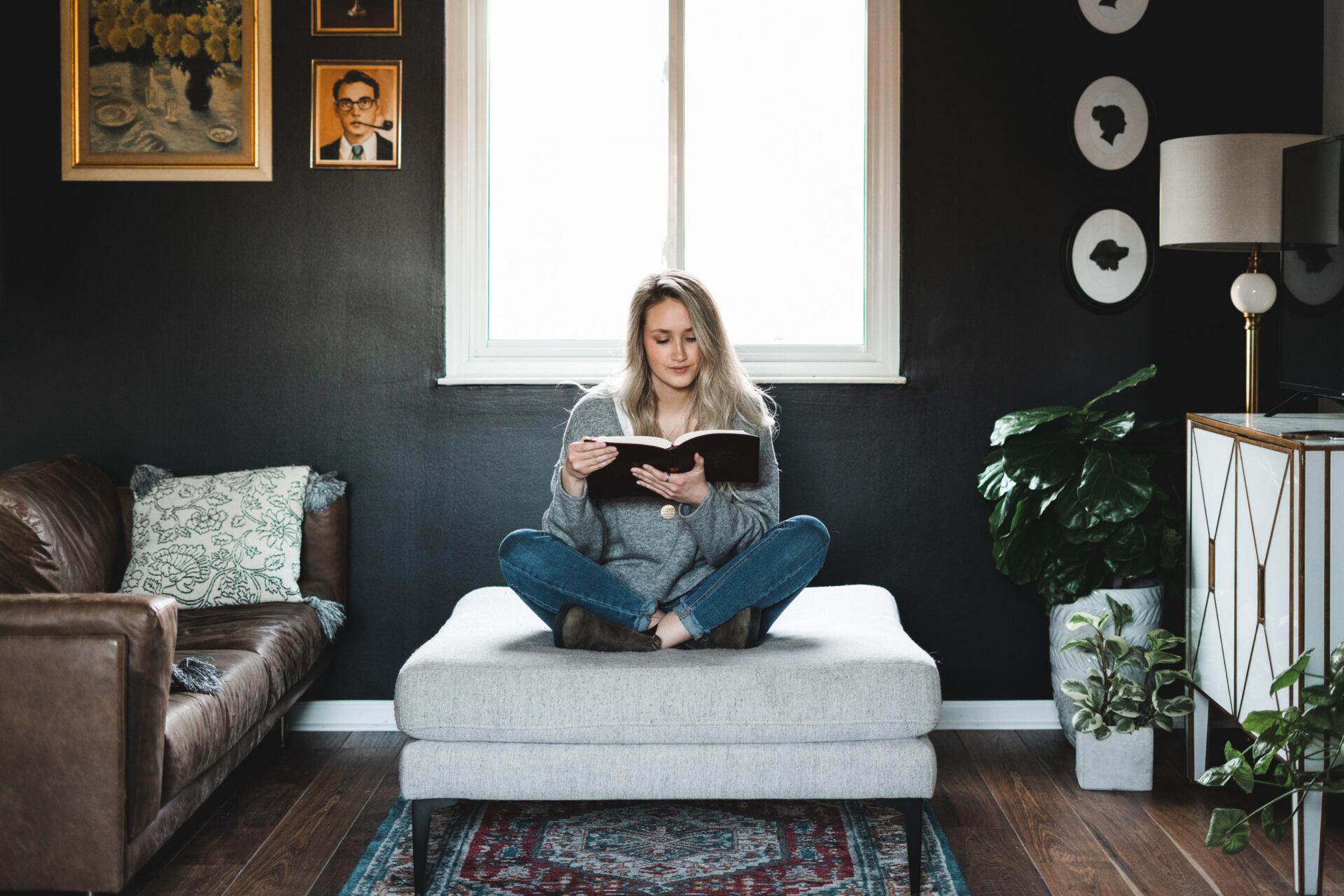 Girl reading Bible on large ottoman