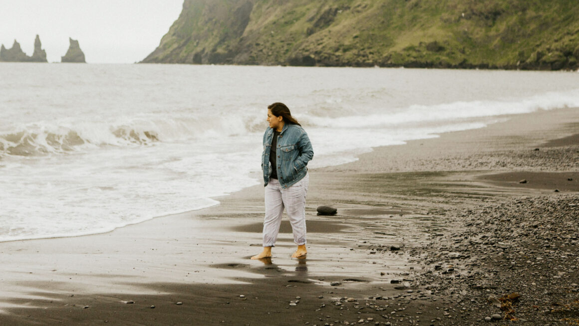 Woman in jacket walking along beach