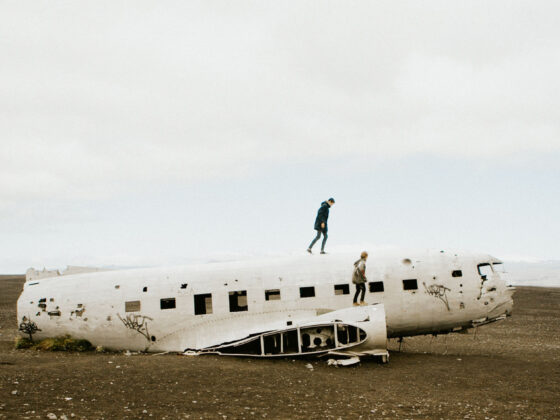 Two people climbing a broken, abandoned plane