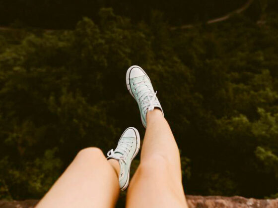 Girls legs and feet dangling over edge of a cliff