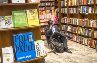 Homem sentado numa livraria lendo