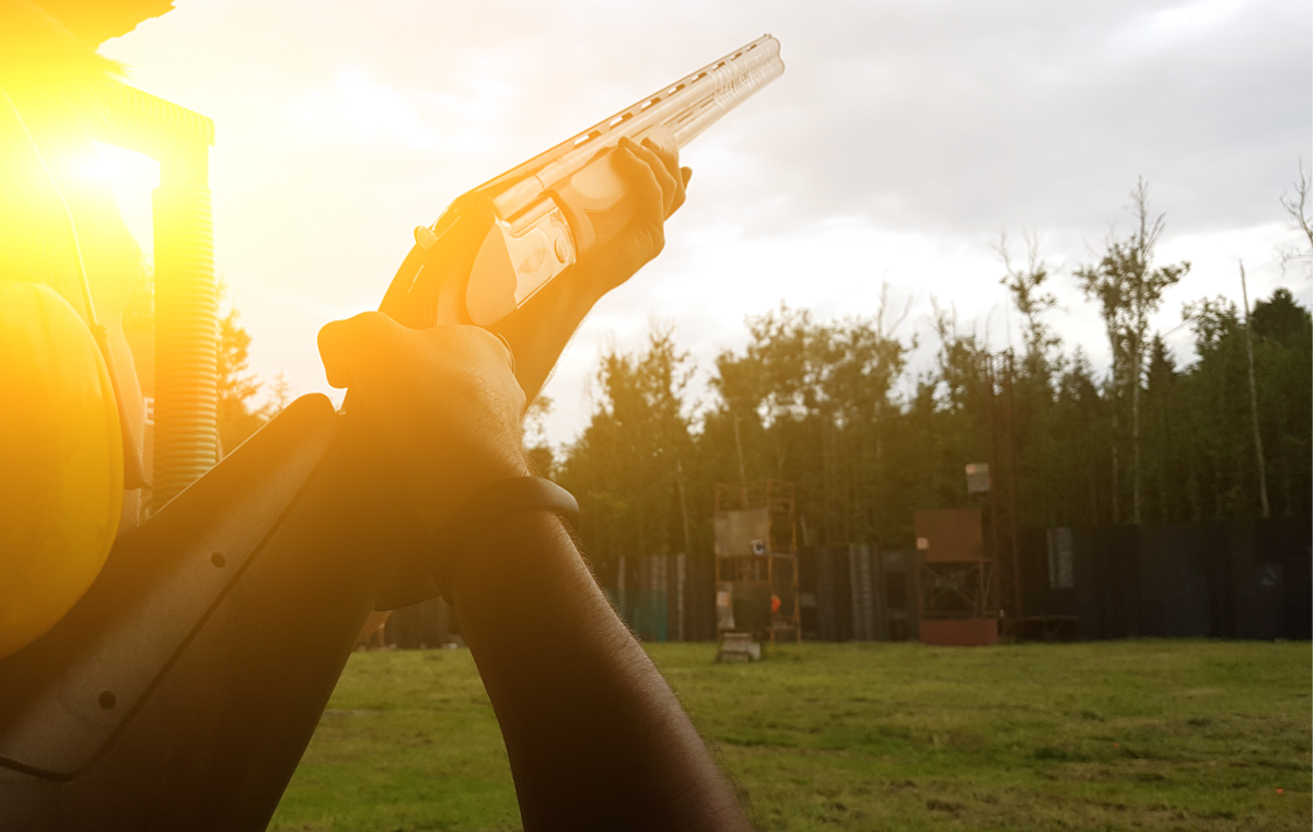 Over-the-shoulder View of Skeet Shooter Holding Shotgun Aimed Upward